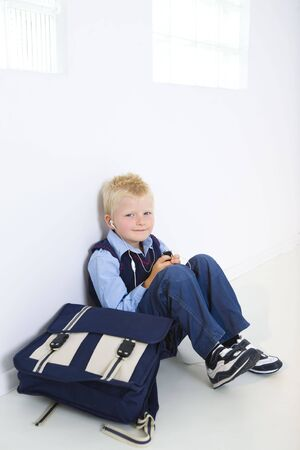 Smiling young schoolboy sitting on the floor with schoolbag. He listening music by earphones. Hes looking at camera. photo
