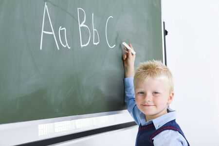 grade schooler: Young smiling boy writing alphabet on chalkboard. Hes looking at camera.