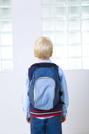 grade schooler: Young schoolboy with backpack. He standing back to the camera. Rear view. Stock Photo