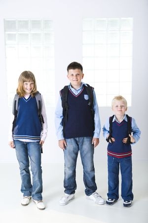schooltime: Three schoolchildren standing in front of windows. They looking at camera. Stock Photo