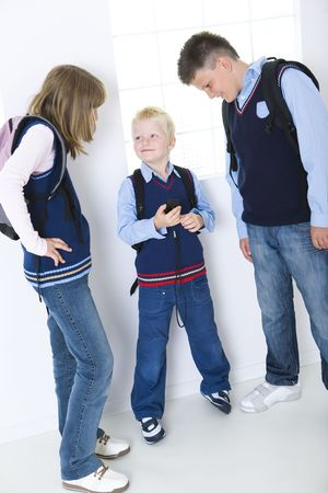 Three schoolchildren standing at corridor in front of window. Younger schoolchild showing something in cellphone. Stock Photo - 3598862