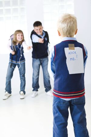 Two schoolmate have a good laugh at younger schoolchild. Younger schoolchild have sticky a note kick me on a back. Focused on younger schoolchild.