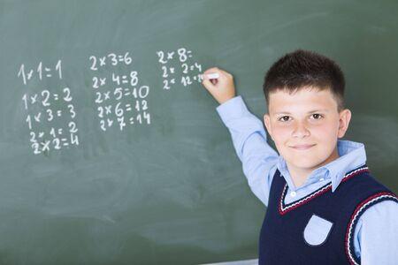 multiplicaci�n: Alumno de pie y escribir algo sobre el pizarr�n. �l  's buscando en la c�mara.
