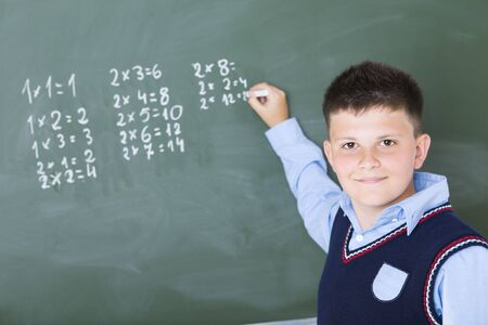 Schoolboy standing and writing something on chalkboard. Hes looking at camera.
