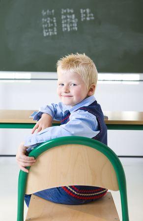 grade schooler: Smiling schoolboy sitting in bench opposite chalkboard. Hes looking at camera.