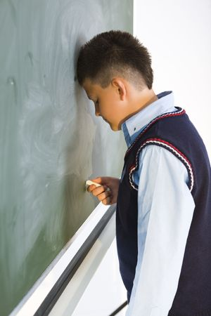 Schoolboy standing at chalkboard and holding chalk in hand. Side view. Stock Photo