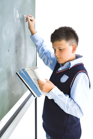 Schoolboy standing at chalkboard and rewriting something from book. Side view. Stock Photo