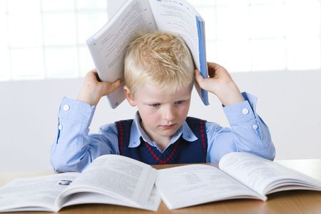 grade schooler: Young boy sitting at desk and reading books. One book holding on head. Front view.
