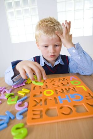 grade schooler: Young boy sitting at desk and making letters jigsaw. Front view.