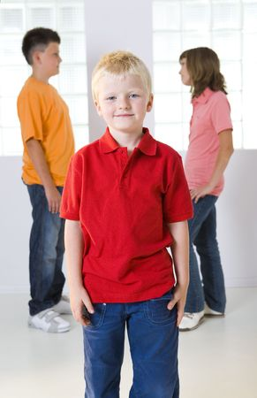 red tshirt: Three children standing in front of windows. In front standing younger boy in the red T-shirt, in the background standing boy and girl and they speak each other. Focused on boy in red T-shirt.