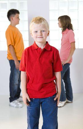 Tre bambini in piedi di fronte a finestre. Di fronte permanente giovani ragazzo in rosso T-shirt, in background in piedi ragazzo e una ragazza e parlano l'un l'altro. Incentrata sul ragazzo in rosso T-shirt.