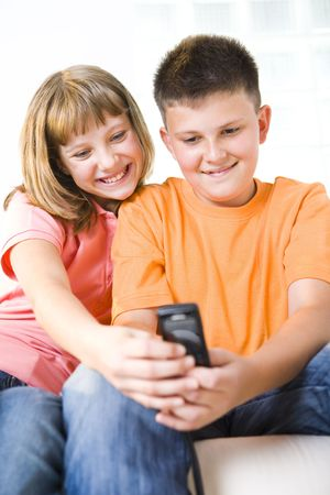 Young girl and boy sitting and watching something in cellphone. Front view. photo