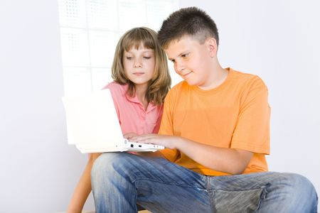 Young boy showing to girl something in laptop. photo