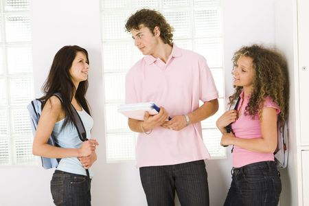 schoolmate: Three schoolmate standing near window and talking. A boy holding notebooks and looking at girl in blue shirt. Front view.
