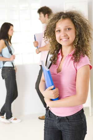 schoolmate: Three schoolmate standing near window. A boy holding notebooks and talking with girl in blue shirt. A girl in ping shirt smiling and looking at camera. Focused on girl in pink shirt. Stock Photo