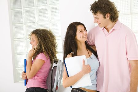 schoolmate: Three schoolmate standing near window. Girls holding notebooks. A boy embracing one of girls and talking. Girl in pink shirt talking by mobile phone. Stock Photo