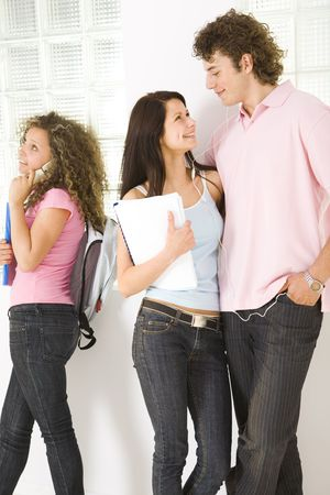 schoolmate: Three schoolmate standing near window. Girls holding notebooks. A boy embracing one of girls and listening to music by headset. Girl in pink shirt talking by mobile phone. Front view. Stock Photo
