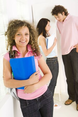 schoolmate: Three schoolmate standing near window. Girls holding notebooks. A boy talking with one of girls. Focused on girl in pink shirt.