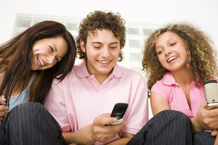 Three happy friends sitting and looking at mobilephone. A boy holding mobile phone. Low angle view. photo