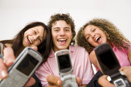Three happy friends sitting and showing mobile phone to the camera. Looking at camera. Low angle view. Stock Photo