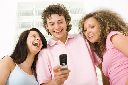 Three happy friends standing and looking at mobilephone. A boy holding mobile phone. Low angle view. photo