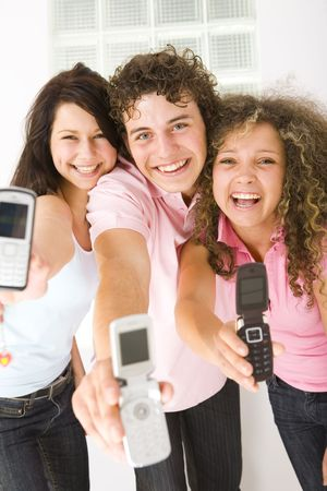 Three happy friends standing and showing mobile phone to the camera. Looking at camera. Low angle view. photo