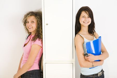shool: Two happy schoolgirl standing and leaning for shool locker. One of them holding notebook and mobilephone. looking at camera.