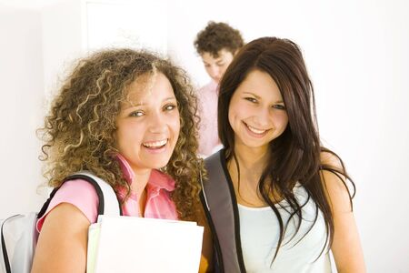 Three schoolmate standing at hollway. Two girls smiling and looking at camera. Focused on the girls. Front view. Stock Photo - 3598883