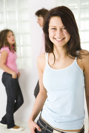 Three friends standing near window. A boy talking with girl in pink shirt. A girl in blue shirt smiling and looking at camera. Focused on girl in blue shirt. photo