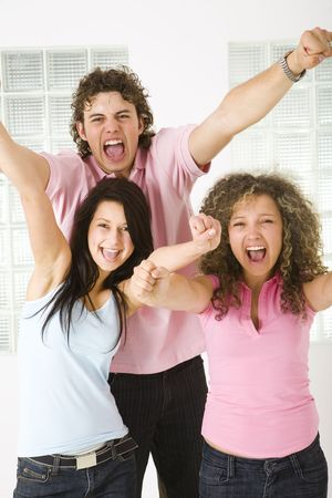 Three friends screaming with raised hands. Looking at camera. Front view. photo