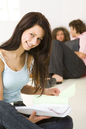 Three schoolmate holding a notebooks and sitting on the floor. A boy talking with girl in pink shirt. A girl in blue shirt smiling and looking at camera. Focused on girl in blue shirt. photo
