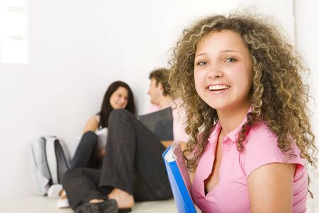 Three schoolmate holding a notebooks and sitting on the floor. A girl in pink shirt smiling and looking at camera. A boy talking with second girl . Focused on girl in pink shirt. photo