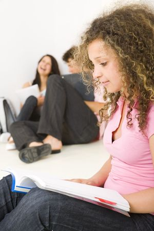 Three schoolmate holding a notebooks and sitting on the floor. A girl in pink shirt reading a notes. A boy talking with second girl . Focused on girl in pink shirt. Stock Photo - 3598922