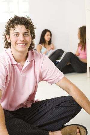 Three friends sitting on the floor. A girls talking with themselves. A boy smiling and looking at camera. Focused on a boy.  photo