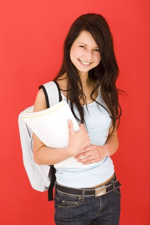 Young happy schoolgirl with backpack, holding notebook. Looking at camera. Front view. photo