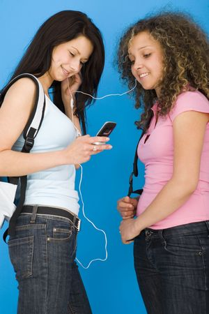 Young happy schoolgirls with backpack listening to music by headset. one of they holding mobile phone. Side view. photo