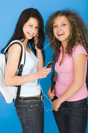Young happy schoolgirls with backpack listening to music by headset. one of they holding mobile phone. Looking at camera. Side view.