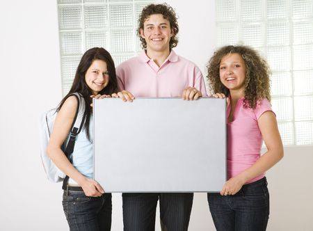 Three happy friends holding grey table. Looking at camera. Front view. photo