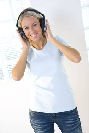Young smiling woman listening to music by headphones. Shes looking at camera. Front view. photo