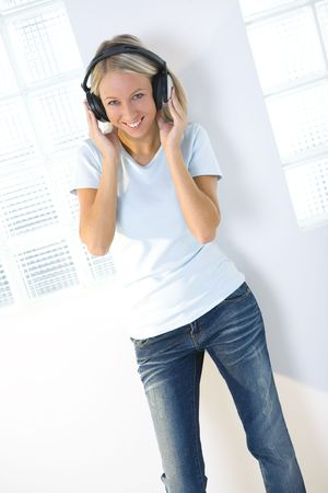 Young smiling woman listening to music by headphones. She's looking at camera. Front view. Stock Photo - 3608504