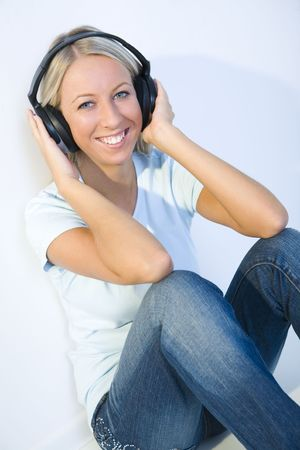 Young smiling woman sitting on the floor and listening to music by headphones. Shes looking at camera. photo