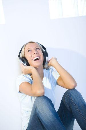 Young smiling woman sitting on the floor and listening to music by headphones. She's looking up. Stock Photo - 3608341