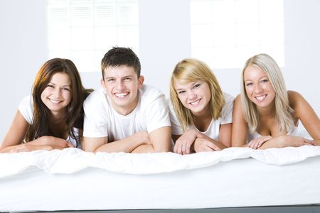 Happy friends lying in bed and looking at camera. Front view. photo
