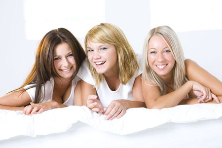 Three girl friends lying in bed and looking at camera. Front view. Stock Photo - 3608512