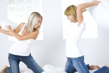 pillow fight: Two happy girl friends fighting a pillows. Theyre kneeling on bed. Stock Photo