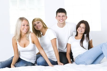 Group of young smiling friends sitting on bed and looking at camera. They have on white t-shirt. Front view. photo