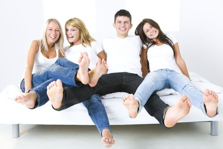 Group of young smiling friends sitting on bed with extended legs. Theyre looking at camera. They have on white t-shirt. Front view.