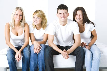 Group of young smiling friends sitting on a couch and looking at camera. Front view. photo