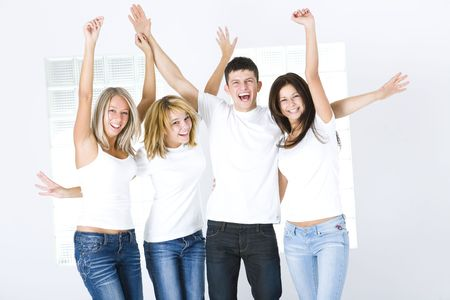 Group of young happy friends with upraised hands. Theyre looking at camera. They have on white t-shirt. Front view.