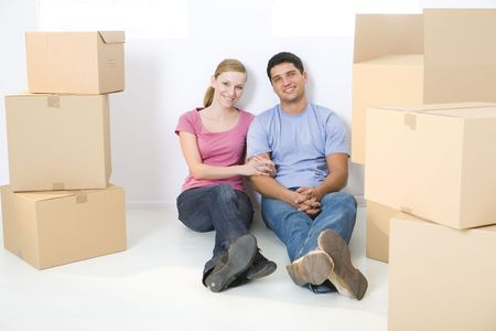unpacking: Young couple sitting on the floor between cardboard boxes. Theyre looking at camera. Front view.